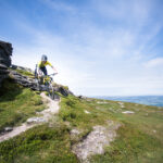 A picture of a mountain biker descending the Moray Coastal Path