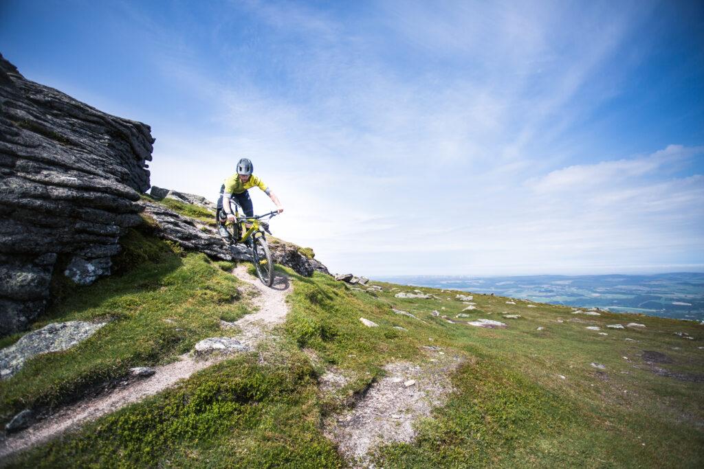 A female mountain biker descending a coastal path in Moray Speyside